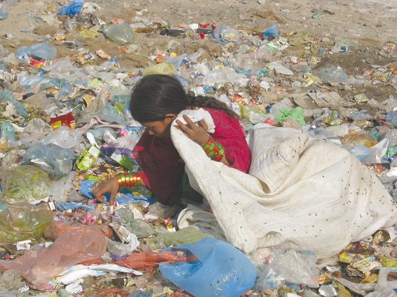 Image of Pakistani girl searching through rubbish