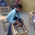 School children helping to paint the new furniture